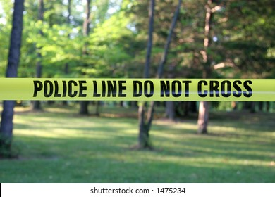Police Do Not Cross – yellow plastic tape in a forest.