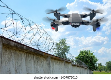 Police drone patrols the area across the sky. Guarding the wall with barbed wire drone with blue and red beacon.