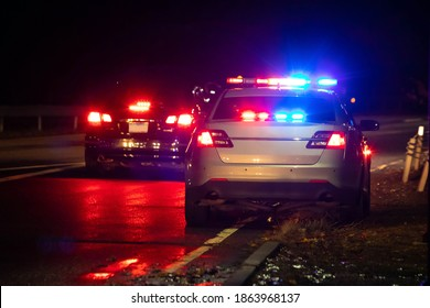 Police emergency flash lights at night from the back on highway road