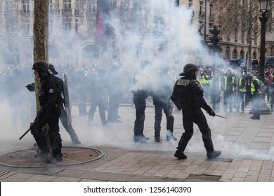 "Police force and tear gas during the ""Yellow Vests"" antigovernment protest in the French capital. Paris, France - December 8, 2018"