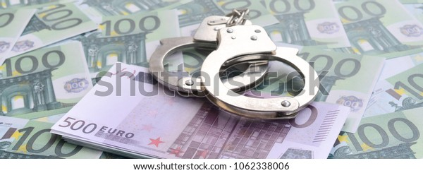 Police handcuffs lies on a set of green monetary denominations of 100 euros. A lot of money forms an infinite heap