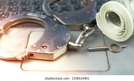 Police Handcuffs with roll money on the laptop keyboard.