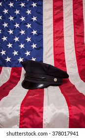 A police hat on an American flag background.