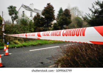 """Police """"Inner Cordon"""" tape is stretched across a road at the scene of a murder investigation."""