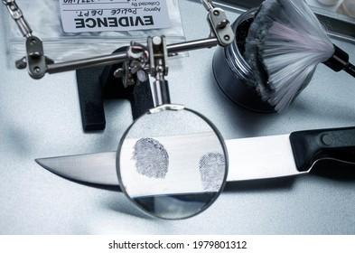 Police investigation of fingerprint on a knife, concept image