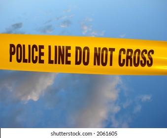 Police line do not cross yellow warning tape over blue sky
