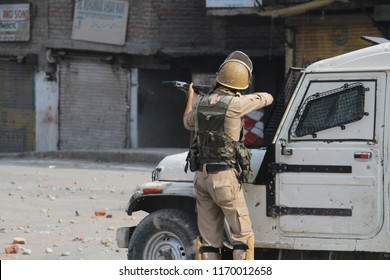 A police man aiming at Kashmiri Muslim protesters with a pellet gun during the clashes erupted between the Indian government forces and protesters, on 22 August 2018, at South Kashmir's Anantnag town.