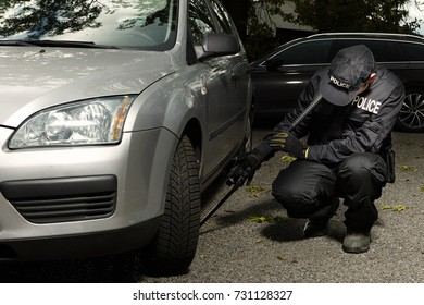 Police man checking car floor with inspection mirror for threats of explosives