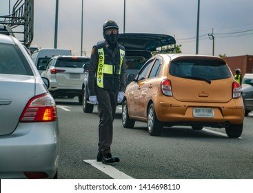 A police man with a face mask checks the traffic on the highway. Policeman work in the middle of a road.