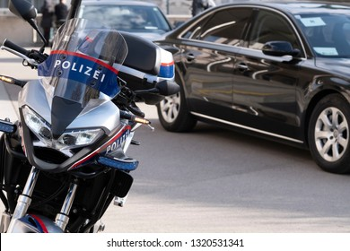 Police motorcycle on the street and government column behind.