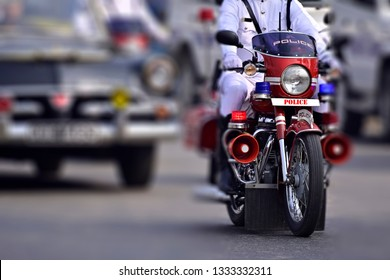 "Police is moving riding motorcycle on street. ""Police"" text in red in front of motorcycle against white is written using photo processing software."