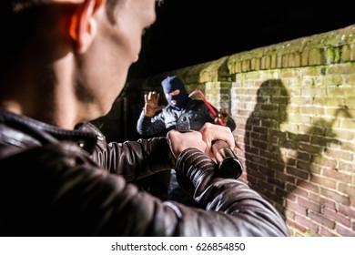 Police Officer Aiming Gun Towards Scared Burglar At Night