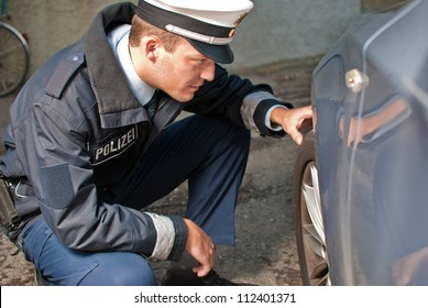Police officer is checking a tire of a vehicle
