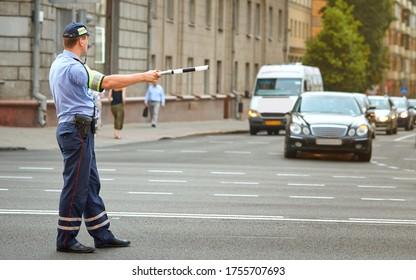 警官が警棒で市内の交通を指示する。 交通警察は通りの交差点、ラッシュアワーで車を調整する。 交通規制の警官