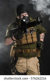Police officer in gas mask with assault rifle. Uniform conforms to elite task force of the United States. Shot in studio.