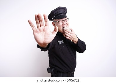 Police officer gesturing to stop while eating donut.