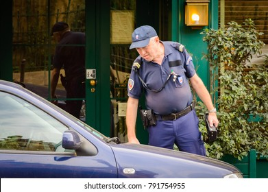 Police officer giving a ticket fine for parking violation. The policeman checks the parking time of the car in paid street parking. Paris, France, October 04, 2014