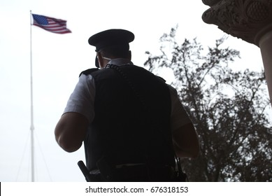 Police Officer / Guard In Front Of American Flag