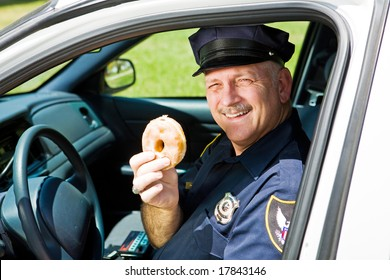 Police officer in his squad car holding a doughnut.