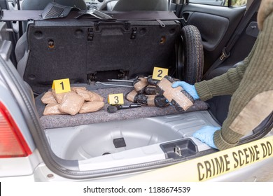 Police officer holding drug package discovered in the trunk of a car