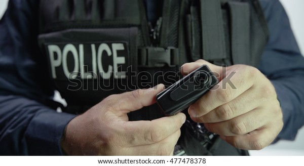Police officer holding Law Enforcement body camera video recorder