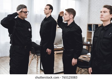 The police officer instructs the subordinates in the police station. This is a large bright room. Men working together on the protection of public order.