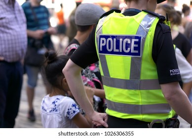 Police officer on duty on a city centre street during special event.