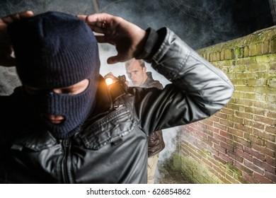Police Officer Pointing Gun Towards Busted Masked Burglar