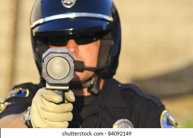 a police officer pointing his radar gun at speeding traffic.