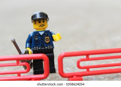 Police officer, policeman with mobile phone standing behind roadblock, fence. Toy, macro photography, close up, editorial image.