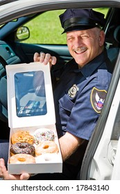 Police officer sitting in his squad car with a box of donuts.