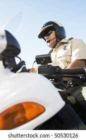 Police officer sitting on motorcycle, low angle view, (low angle view)