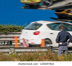 Police officer with speed camera monitors the speed of vehicles on the edge of the highway