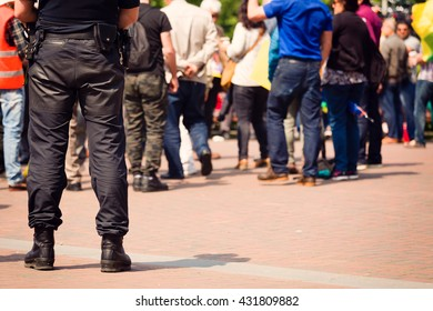 Police officer surveilling a group of people in a public place. Selective focus.