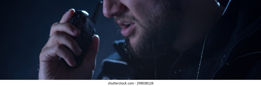Police officer is using his shortwave radio during intervention