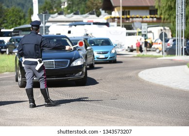 Police officer with a warning sign telling a car to stop. Italian police man during a traffic checkpoint in the midddle of the road. Street control and terrorism prevention.