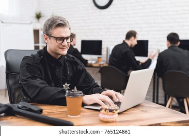 A police officer works for a laptop in a police station. On his desk lie donuts and a cup of coffee. He's in a good mood.