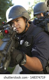 Police officers aiming with guns