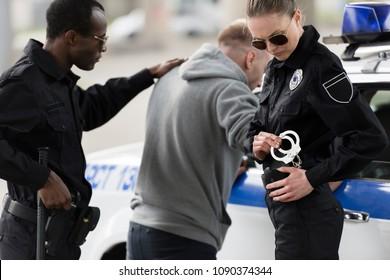 police officers arresting male bandit near car
