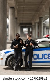 police officers with coffee and doughnuts standing next to car