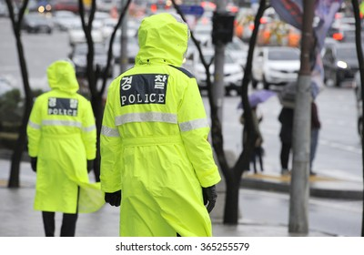 Police officers in the rain at a street in Seoul, South Korea