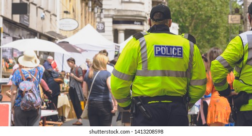 Police Officers Are Watching The Crowd, Rear view of Police and blurred street crowd, Captured in Bristol England 2019, Shallow Depth of Field