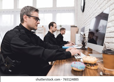 Police officers work at a computer in the police station. On the table lie donuts and stand glasses with coffee. In the hands holding a folder with papers.