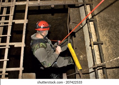 Police rescue worker runs the rope into the flooded old mine