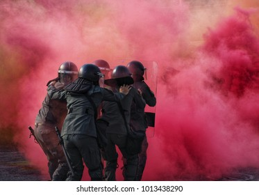 Police in Riot Gear surrounded by tear gas and pink color smoke bomb in tactical training