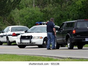 Police roadblock, officer talking to motorist