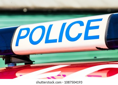 Police sign with blue lights on top of patrol car.