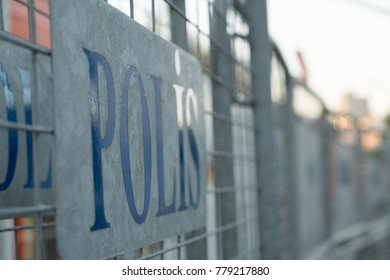 Police Sign on Metal Barriers Outside of Station in Morning