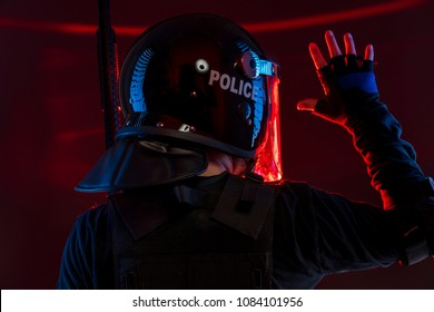 police signaling to their comrades, policeman with full equipment for anti-riot, Law enforcer in protective uniform ready for crowd control isolated on black