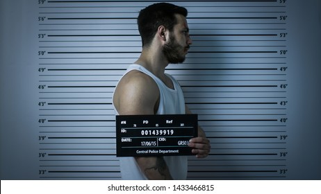 In a Police Station Arrested Beaten Man Poses for Side View Mugshot. He Wears Singlet, is Heavily Bruised and Holds Placard. Height Chart in the Background. Shot with Dark Cold Lights, Vignette Filter